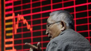 An investor chats in front of an electronic board showing stock information at a brokerage house in Beijing, August 26, 2015. Asian shares struggled on Wednesday as investors feared fresh rate cuts in China would not be enough to stabilise its slowing economy or halt a stock collapse that is wreaking havoc in global markets. REUTERS/Jason Lee  - RTX1PNY3