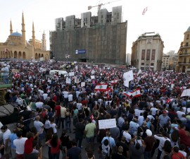 """People carry Lebanese national flags and banners as they take part in an anti-government protest at Martyrs' Square in downtown Beirut, Lebanon August 29, 2015. Thousands of protesters waving Lebanese flags and chanting anti-government slogans converged on a square in central Beirut on Saturday for a rally against political leaders they say are incompetent and corrupt.Their """"You Stink"""" protest campaign was mobilised after the government failed to solve a crisis in trash disposal, leaving piles of refuse rotting in the summer sun. REUTERS/Jamal Saidi - RTX1Q75O"""