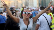 """A protester wears sunglasses decorated with Lebanese national flags as she takes part in an anti-government protest at Martyrs' Square in downtown Beirut, Lebanon August 29, 2015. Thousands of protesters waving Lebanese flags and chanting anti-government slogans converged on a square in central Beirut on Saturday for a rally against political leaders they say are incompetent and corrupt.Their """"You Stink"""" protest campaign was mobilised after the government failed to solve a crisis in trash disposal, leaving piles of refuse rotting in the summer sun. REUTERS/Hasan Shaaban - RTX1Q7G3"""