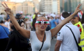 "A protester wears sunglasses decorated with Lebanese national flags as she takes part in an anti-government protest at Martyrs' Square in downtown Beirut, Lebanon August 29, 2015. Thousands of protesters waving Lebanese flags and chanting anti-government slogans converged on a square in central Beirut on Saturday for a rally against political leaders they say are incompetent and corrupt.Their ""You Stink"" protest campaign was mobilised after the government failed to solve a crisis in trash disposal, leaving piles of refuse rotting in the summer sun. REUTERS/Hasan Shaaban - RTX1Q7G3"