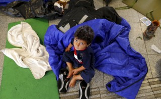 A Syrian migrant child sits on the floor while waiting to leave Hungary outside a train station in Budapest, Hungary August 29, 2015. Picture taken August 29, 2015. REUTERS/Laszlo Balogh - RTX1QAWV