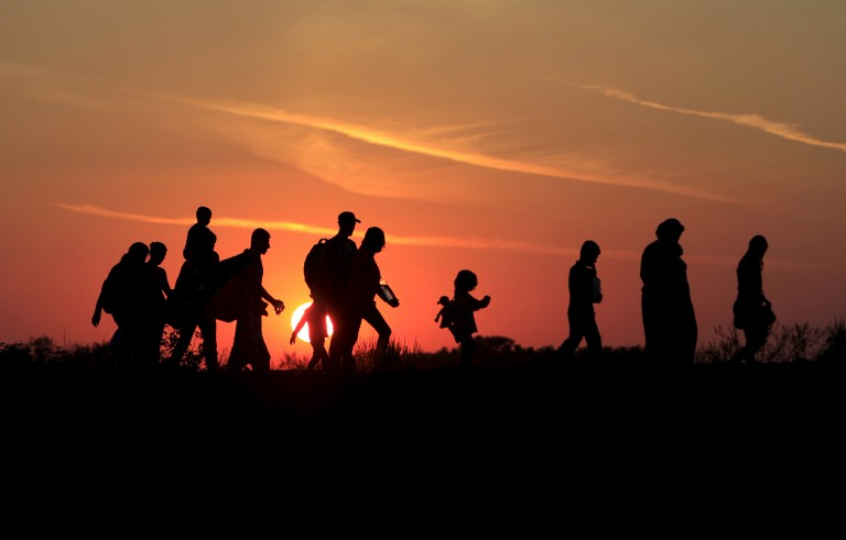 Migrants walk along in the sunset after crossing into Hungary from the border with Serbia near Roszke, Hungary, August 30, 2015. Photo by Bernadett Szabo/Reuters.