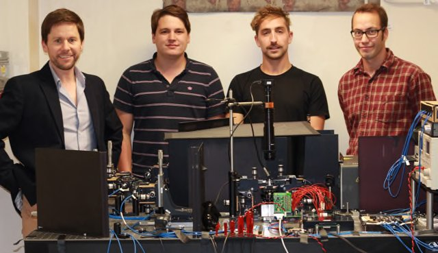 Dr. Anthony Laing with his students Chris Sparrow, Jacques Carolan, and Chris Harrold (left to right) stand behind the universal linear optical processor, with its electronics, photon source and photon detection system. Photo by University of Bristol