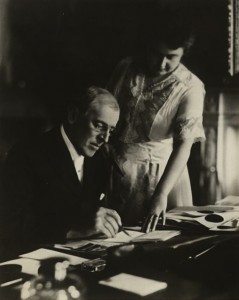 President Woodrow Wilson, seated at desk with his wife, Edith Bolling Galt, standing at his side. First posed picture after Mr. Wilson's illness, White House, June 1920. Courtesy the Library of Congress