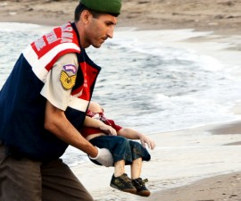 A Turkish police officer carries a young refugee, who drowned in a failed attempt to sail to the Greek island of Kos, in the coastal town of Bodrum, Turkey, Sept. 2, 2015. Photo by Nilufer Demir/DHA/via Reuters