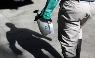 Contra Costa County Mosquito and Vector Control District technician David Wexler carries a container of BVA Larvacide Oil before spraying a catch basin with standing water and mosquito larvae on June 29, 2012 in Pleasant Hill, California. Photo by Justin Sullivan/Getty Images