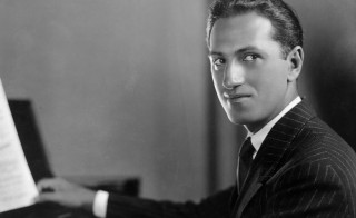 circa 1925:  Portrait of American composer George Gershwin (1898 - 1937) seated at a piano in a pinstriped suit.  (Photo by Hulton Archive/Getty Images)
