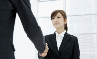 Woman shaking hands in suit. Related words: jobs, job search, interview. Photo by Indeed/Getty Images