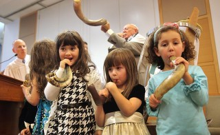 Rabbi Jay Perlman, far left, looks on as sisters Rachel and Allyson Faberman and Sydney Kaufman blew their shofars during a children's Yom Kippur service at Temple Beth Shalom in Needham, Mass. on October 4 2014. Photo by Wendy Maeda/The Boston Globe via Getty Images