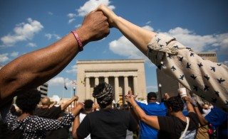 People hold hands during a rally lead by faith leaders in front of city hall calling for justice in response to the death of Freddie Gray on May 3, 2015 in Baltimore. Photo by Andrew Burton/Getty Images