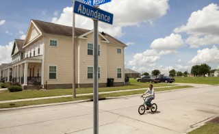 NEW ORLEANS, LA - MAY 28: A young boy rides his bike through a housing development that was built in the Upper Ninth Ward after Katrina destroyed neighborhoods when levies broke, on May 28, 2015 in New Orleans, Louisiana. Low-income residents who lost their homes live here and either rent or own their homes. It has been almost 10 years since hurricane Katrina hit New Orleans, devastating many neighborhoods. Rebuilding has been slow and controversial. (Photo by Melanie Stetson Freeman/The Christian Science Monitor via Getty Images)