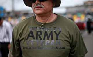 U.S. Army veteran Hector Lopez participates in a protest by deported military personnel at the U.S.- Mexico border in March 2014 in Tijuana, Mexico.  Photo by Sandy Huffaker/Getty Images