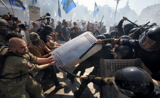 KIEV, UKRAINE - AUGUST 31: Protestors clash with National Guards troops nearby Verkhovna Rada building on August 31, 2015 in Kiev, Ukraine. 120 were wounded and 1 is dead in clashes after lawmakers gave initial approval to changes of Constitution of Ukraine granting more autonomy to pro-Russian separatists in eastern Ukraine Attackers threw a hand grenade at National Guard troops guarding the building of Rada. (Photo by Ivan Kovalenko/Kommersant Photo via Getty Images)
