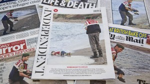 The front pages of some of Britain's daily newspapers showing an image of the body of Syrian three-year-old boy Aylan are pictured in London, on September 3, 2015. The image spread like lightning through social media and dominated front pages from Spain to Sweden, with commentators unanimous it had rammed home the horrors faced by those fleeing war and conflict in the Middle East and Africa. AFP PHOTO/JUSTIN TALLIS        (Photo credit should read JUSTIN TALLIS/AFP/Getty Images)