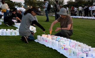 This picture taken on September 4, 2015, shows people lighting candles to celebrate at Naraha town in Fukushima as the Japanese government lifts an evacuation order to Naraha near the crippled nuclear plant, after a clean-up programme has lowered radiation levels in the area. Among communities where the entire population was forced to evacuate after the nuclear crisis started in March 2011, Naraha is the first town to allow all of its residents to return home permanently.   AFP PHOTO / JIJI PRESS    JAPAN OUT        (Photo credit should read JIJI PRESS/AFP/Getty Images)