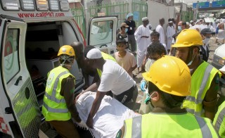 Saudi emergency personnel and hajj pilgrims load a wounded person into an ambulance at the site where hundreds were killed and wounded in a stampede in Mina, near the holy city of Mecca in Saudi Arabia on Sept. 24. Photo by STR/AFP/Getty Images