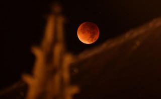 "A swollen ""supermoon"" is seen bathed in the blood-red light during the stages of a total eclipse above Saint-Michel church in Bordeaux, southwestern France, early on September 28, 2015. Stargazers were treated to a rare astronomical event when a swollen ""supermoon"" and lunar eclipse combined for the first time in decades, showing the planet bathed in blood-red light. AFP PHOTO / NICOLAS TUCAT        (Photo credit should read NICOLAS TUCAT/AFP/Getty Images)"