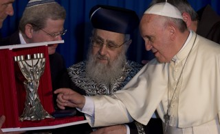 Pope Francis (R) receives a gift from Israeli Sephardi Chief Rabbi, Yitzhak Yosef (C), during a visit to the Heichal Shlomo Center in Jerusalem on May 26, 2014. Photo by Andrew Medichini  /AFP/Getty Images)