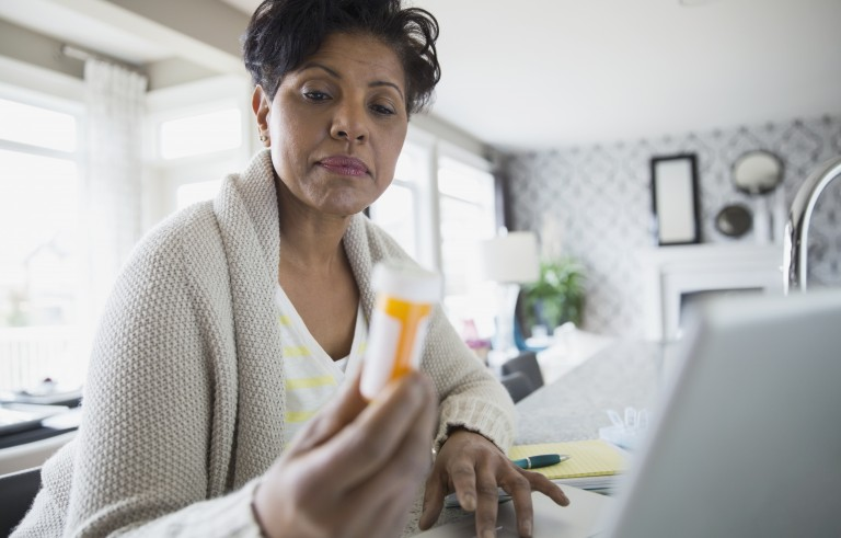Woman reading prescription bottle label at laptop. Related words: medication, meds, drugs, pills. Photo by Hero Images/Getty Images