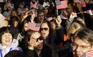 New U.S. citizens celebrate after taking the oath of citizenship during a naturalization ceremony beneath the Statue of Liberty in New York on Oct. 28,  2011. Photo by Mike Segar/Reuters