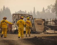 Firefighters survey a destroyed home at the so-called Valley Fire near Middleton, California September 14, 2015. A Northern California wildfire ranked as the most destructive to hit the drought-stricken U.S. West this year has claimed one life and burned at least 400 homes to the ground, fire officials reported on Monday, saying they expected the property toll to climb.  REUTERS/David Ryder - RTS138H