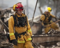 Firefighters search for victims in the rubble of a home burnt by the Valley Fire in Middletown, California, September 14, 2015. The Northern California wildfire ranked as the most destructive to hit the drought-stricken U.S. West this year has killed one woman and burned some 400 homes to the ground, fire officials said on Monday, and they expect the property toll to climb.  REUTERS/David Ryder - RTS1494