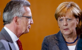 German Interior Minister Thomas de Maiziere stands with Chancellor Angela Merkel as they arrive for the special cabinet meeting on migrants' situation, in the Chancellery in Berlin, Germany, September 15, 2015. REUTERS/Hannibal Hanschke  - RTS1747
