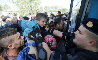 A Croatian policeman helps a boy as migrants board a bus in Tovarnik, Croatia, September 17, 2015. The European Union's migration chief Dimitris Avromopoulos rebuked Hungary on Thursday for its tough handling of a flood of refugees as asylum seekers thwarted by a new Hungarian border fence and repelled by riot police poured into Croatia, spreading the strain. REUTERS/Antonio Bronic - RTS1KTH