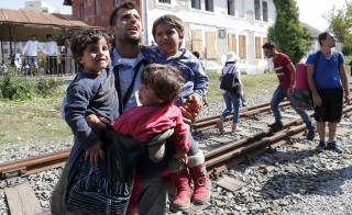 A migrant carries three children as others scramble aboard a train at the station in Beli Manastir, Croatia September 18, 2015. Migrant numbers in Europe will build up in coming days and their flows may fragment further into new routes, the U.N. refugee agency said on Friday, urging the European Union to grasp a last chance to resolve the refugee crisis next week. REUTERS/Laszlo Balogh - RTS1QFV