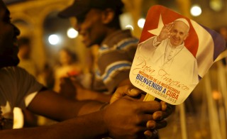 Young Catholic faithful holds a sign reads: 'Welcome Pope Francis' during a vigil to pray in front of Havana's Cathedral in Havana September 18, 2015. The Obama administration announced wide-ranging new rules on Friday to ease trade, travel and investment restrictions with Cuba, the latest effort to chip away at the long-standing U.S. economic embargo amid a diplomatic thaw between the two former Cold War foes.The announcement came just as Pope Francis, who played an instrumental role in the diplomatic opening late last year, prepares to visit Cuba this weekend before heading to the United State next week. The Vatican has long condemned the embargo against Cuba. REUTERS/Carlos GarciaRawlins - RTS1TVZ