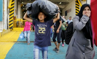 A boy carries a bag while refugees and migrants disembark the Eleftherios Venizelos passenger ship at the port of Piraeus, near Athens Sept. 9, 2015. Over the past nine days, the coastguard estimates Greek authorities have moved close to 18,000 refugees from Lesbos to the mainland. Paul Hanna/Reuters
