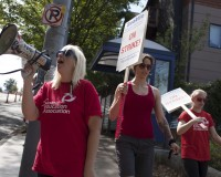 Rosa Powers shouts chants on the megaphone while other teachers walk the picket line as they strike outside Garfield High School in Seattle, Washington September 9, 2015. Classes were cancelled for 53,000 students as Seattle teachers and support staff marched in picket lines on Wednesday on what was supposed to be the first day of school, waging their first such strike in three decades after contract talks between the school district and the teachers' union failed.  REUTERS/Matt Mills McKnight - RTSDZE