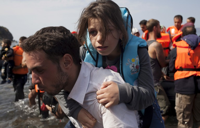 A Syrian refugee carries a young girl moments after arriving on a dinghy on the Greek island of Lesbos on Sept. 10. Most of the people flooding into Europe are refugees fleeing violence and persecution in their home countries who have a legal right to seek asylum, the United Nations said on Tuesday. Photo by Dimitris Michalakis/Reuters