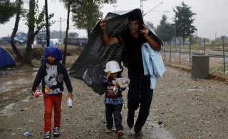 A Syrian refugee covers  his child as they walk towards the border from Greece into Macedonia during a rainstorm, near the Greek village of Idomeni, September 10, 2015. Most of the people flooding into Europe are refugees fleeing violence and persecution in their home countries who have a legal right to seek asylum, the United Nations said on Tuesday. REUTERS/Yannis Behrakis  - RTSJ9C