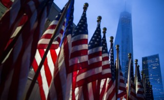 One World Trade Center is seen behind U.S flags on the morning of the 14th anniversary of the 9/11 attacks, in Lower Manhattan in New York September 11, 2015. Relatives of the nearly 3,000 people killed in the Sept. 11, 2001, attacks are due to gather in New York, Pennsylvania and outside Washington on Friday to mark the 14th anniversary of the hijacked airliner strikes carried out by al Qaeda militants. REUTERS/Andrew Kelly - RTSM3K