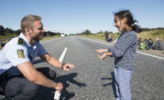 A Danish policeman plays a game with a migrant girl in Padborg, southern Denmark near the German border, on Sept. 9. Many migrants, mainly from Syria and Iraq, have arrived in Denmark over the last few days on their journey to Sweden to seek asylum. Photo by Claus Fisker/Scanpix via Reuters