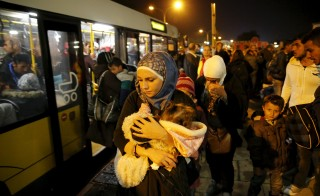 Families board buses to be transported to a Berlin refugee camp after they arrived by train from Austria earlier this month. Photo by Fabrizio Bensch/Reuters
