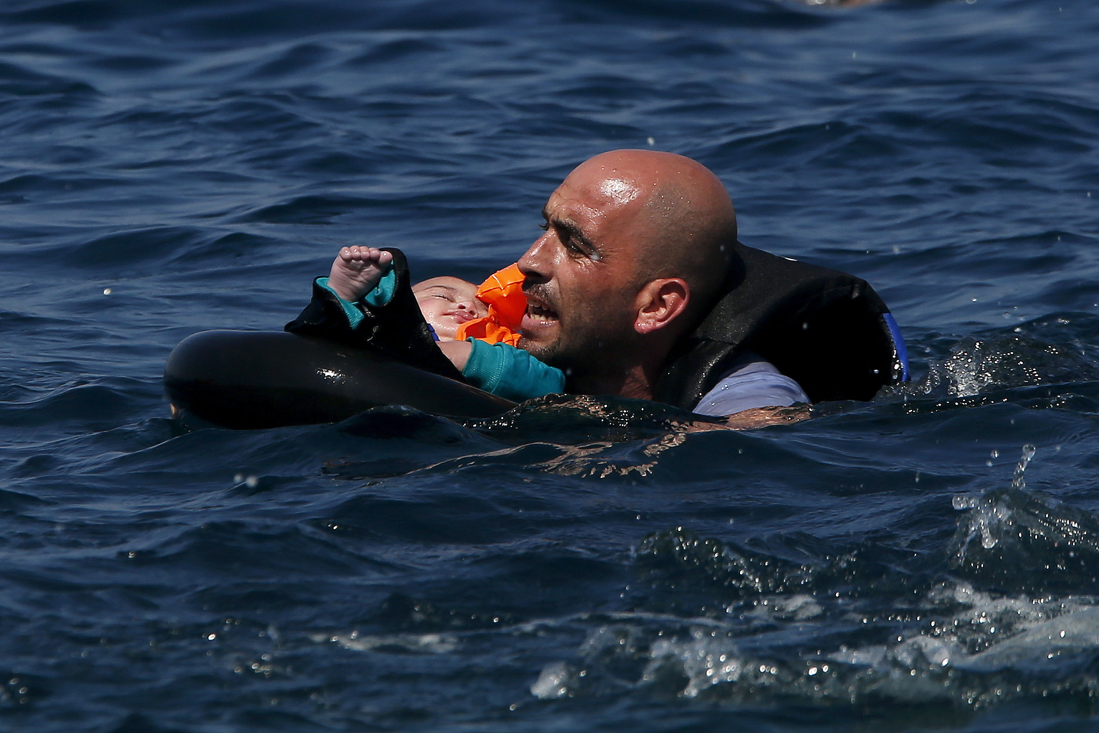 A Syrian refugee holding a baby in a lifetube swims towards the shore after their dinghy deflated some 100m away before reaching the Greek island of Lesbos, September 13, 2015. Of the record total of 432,761 refugees and migrants making the perilous journey across the Mediterranean to Europe so far this year, an estimated 309,000 people had arrived by sea in Greece, the International Organization for Migration (IMO) said on Friday. About half of those crossing the Mediterranean are Syrians fleeing civil war, according to the United Nations refugee agency. Photo by Alkis Konstantinidis/Reuters