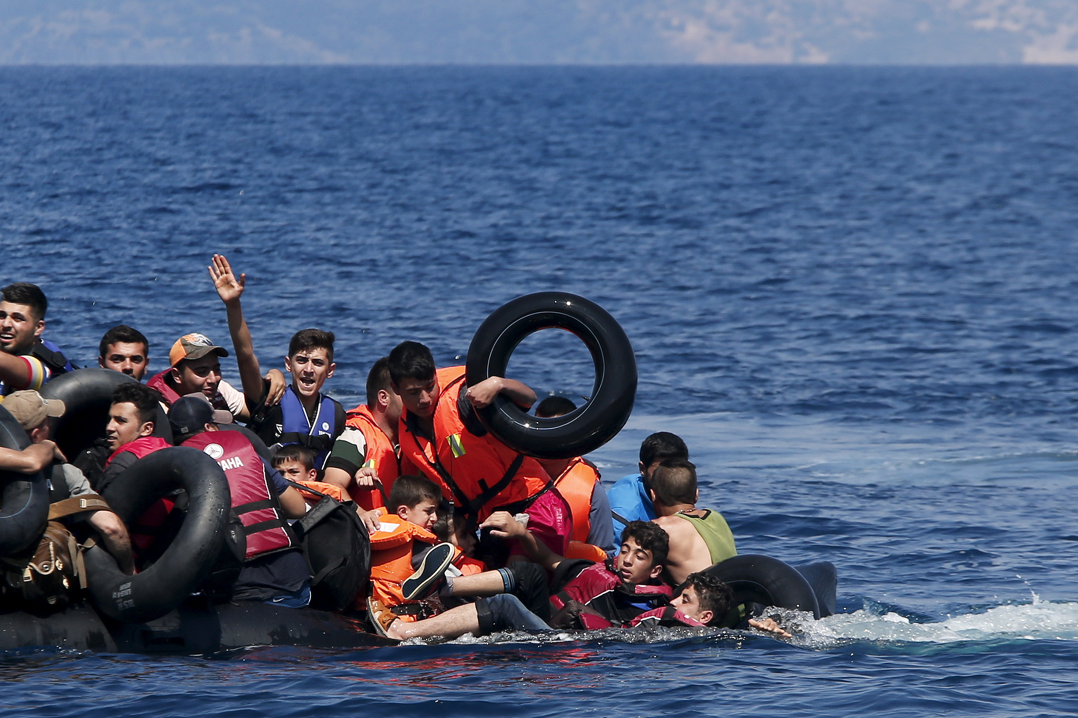 Syrian and Afghan refugees fall into the sea after their dinghy deflated some 100m away before reaching the Greek island of Lesbos, September 13, 2015. Of the record total of 432,761 refugees and migrants making the perilous journey across the Mediterranean to Europe so far this year, an estimated 309,000 people had arrived by sea in Greece, the International Organization for Migration (IMO) said on Friday. About half of those crossing the Mediterranean are Syrians fleeing civil war, according to the United Nations refugee agency. Photo by Alkis Konstantinidis/Reuters
