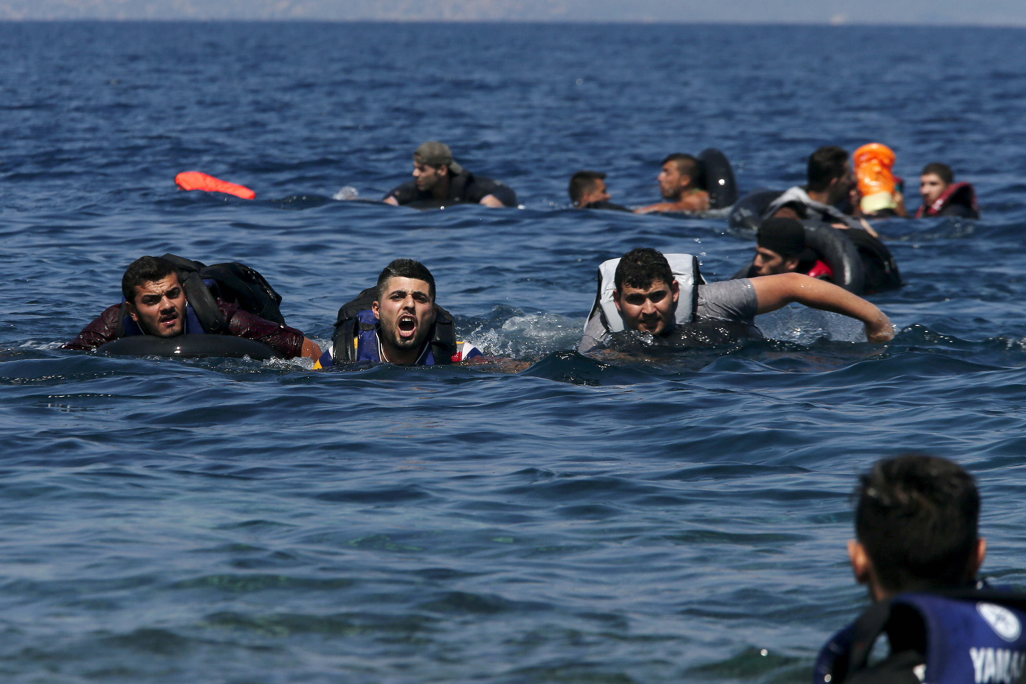 A refugee (2nd L) shouts as he swims towards the shore after a dinghy carrying Syrian and Afghan refugees deflated some 100m away before reaching the Greek island of Lesbos, September 13, 2015. Of the record total of 432,761 refugees and migrants making the perilous journey across the Mediterranean to Europe so far this year, an estimated 309,000 people had arrived by sea in Greece, the International Organization for Migration (IMO) said on Friday. About half of those crossing the Mediterranean are Syrians fleeing civil war, according to the United Nations refugee agency. Photo by Alkis Konstantinidis/Reuters