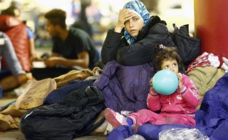 A migrant woman and a child rest at an improvised shelter in the underground parking of a train station in Salzburg, Austria September 13, 2015. As Germany announced it was re-imposing border controls in a bid to slow an influx of migrants, Austria, through which tens of thousands have passed on their way to Germany, was expecting a record number of arrivals on Sunday. More than a week after the two countries threw open their borders to the migrants, Germany said it was reversing course as a temporary measure. Austria's chancellor, however, was quoted as saying that his country would not immediately follow suit.REUTERS/Dominic Ebenbichler - RTSWI5