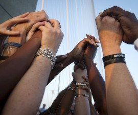 People of different races hold hands as they gather on the Arthur Ravenel Jr. bridge in Charleston, June 21, 2015, after the first service at the Emanuel African Methodist Episcopal Church since a mass shooting left nine people dead. Hundreds of people packed the sweltering Emanuel African Methodist Episcopal Church in Charleston for an emotional memorial service on Sunday just days after a gunman, identified by authorities as Dylann Roof, a 21-year-old white man, shot dead nine black church members.   REUTERS/Carlo Allegri - RTX1HIO6