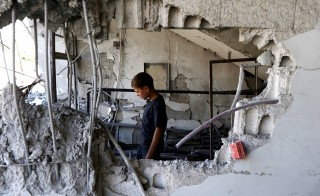 A child inspects a site hit by what activists said was an airstrike by forces loyal to Syria's President Bashar el-Asaad at Arbin town in Damascus countryside, Syria on July 21, 2015. Although the Obama administration is unsure about Moscow's intentions, U.S. officials agreed to hold talks with Russian President Vladimir Putin about his country's military buildup in Syria. Photo by Bassam Khabieh/Reuters