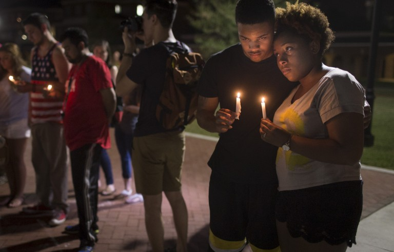 Sheldon Gilton (L) and Brea Butler hold candles during a candlelight vigil for victims of the Thursday night shooting at a movie theater in Lafayette, Louisiana, July 24, 2015. A 59-year-old man who had been committed to a hospital for psychiatric care was identified by authorities as the gunman who fatally shot two people in a rampage at a crowded movie theater in Lafayette before turning the gun on himself as police closed in. REUTERS/Lee Celano      TPX IMAGES OF THE DAY      - RTX1LQFO