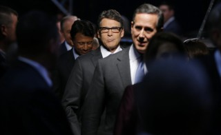 Republican presidential candidates (L-R), Louisiana Governor Bobby Jindal, former Texas Governor Rick Perry and former U.S. Senator Rick Santorum, arrive onstage for the start of a Fox-sponsored forum for lower polling candidates held before the first official Republican presidential candidates debate of the 2016 U.S. presidential campaign in Cleveland, Ohio, August 6, 2015. REUTERS/Brian Snyder  - RTX1NDOK
