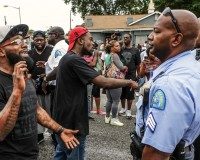 Area residents talk to police after a shooting incident in St. Louis, Missouri August 19, 2015. Police fatally shot a black man they say pointed a gun at them, drawing angry crowds and recalling the racial tensions sparked by the killing of an unarmed African-American teen in nearby Ferguson, Missouri, just over a year ago.  REUTERS/Lawrence Bryant - RTX1OV2H