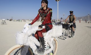 "Bibi rides her unicorn-themed bike on the playa during the Burning Man 2015 ""Carnival of Mirrors"" in the Black Rock Desert of Nevada on Aug. 31. Approximately 70,000 people from all over the world are gathering at the sold-out festival to spend a week in the remote desert to experience art, music and the unique community that develops. Photo by Jim Urquhart/Reuters"