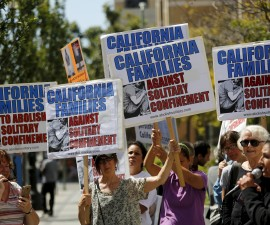 Demonstrators carry signs during a rally at the Elihu Harris state building in Oakland, California, September 1, 2015. California will release hundreds of inmates confined for years in solitary confinement into units where they will live with others, in a sweeping settlement announced Tuesday to reform the practice of keeping prisoners in near-isolation for decades. The settlement ends a lawsuit originally brought by prisoners at the state's Pelican Bay maximum-security facility, where some lived for decades housed alone in their cells for up to 23 hours a day, plaintiffs' lawyers and state officials said. REUTERS/Robert Galbraith - RTX1QNHM