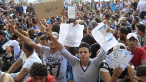 "Refugees raise their documents and railways tickets outside the Keleti station in Budapest, Hungary September 2, 2015. Hundreds of migrants protest in front of Budapest's Keleti Railway Terminus for a second straight day on Wednesday, shouting ""Freedom, freedom!"" and demanding to be let onto trains bound for Germany from a station that has been closed to them by Hungarian riot police officers.  REUTERS/Bernadett Szabo   - RTX1QSEO"