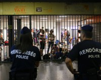 """Hungarian police guard refugees at a makeshift camp in an underground station near the Keleti train station in Budapest, Hungary September 2, 2015. Hundreds of migrants protest in front of Budapest's Keleti Railway Terminus for a second straight day on Wednesday, shouting """"Freedom, freedom!"""" and demanding to be let onto trains bound for Germany from a station that has been closed to them by Hungarian riot police officers.  REUTERS/Leonhard Foeger - RTX1QSV9"""